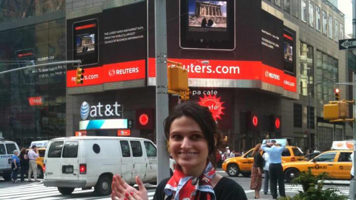 Alina Vandenberghe ở Quảng trường Thời đại (New York), đứng bên dưới một quảng cáo cho ứng dụng Thomas Reuters iPad do cô thiết kế.