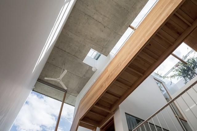 Gỗ là vật liệu nội thất chính tạo nên không gian ấm cúng, thân thuộc, kết hợp chất liệu bê tông thô từ trần nhà và sàn đá đen. Bên cạnh đó, việc trồng xen kẽ cây xanh và thêm các khu sân vườn trong nhà có thể giúp tăng sự tương tác giữa con người và thiên nhiên.