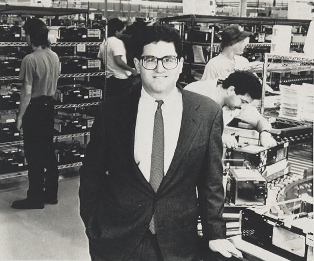 MichaelDellđứng cạnhmột dây chuyềnsản xuấttại nhà máycủa mìnhở Austin.