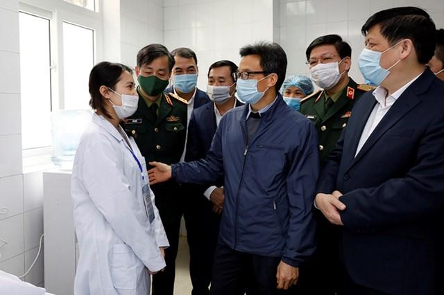 Phó thủ tướng Vũ Đức Đam động viên một trong ba tình nguyện viên đầu tiên tiêm thử nghiệm vaccine Covid-19 do Việt Nam sản xuất.