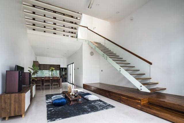 Giải pháp thiết kế lệch tầng này ngay từ tầng 1 đã tạo ra phân chia ước lượng giữa khu vực phòng khách với phòng ăn, bếp qua chiều cao trần nhà đơn giản mà vẫn có sự gắn kết.Cầu thang sử dụng thang bản thép tạo cảm giác nhẹ nhàng, thông gió xuyên phòng và không cản tầm nhìn các không gian trong nhà.