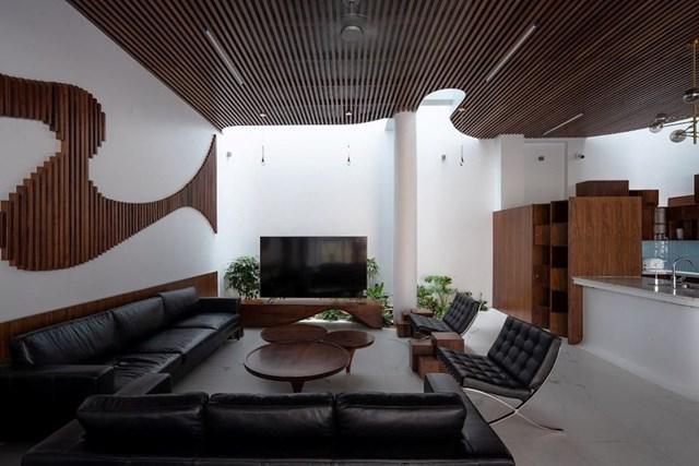 Tầng một là không gian của phòng khách, khu vực ăn, bếp và khoảng sân vườn trước nhà. Một trong những điểm nhấn của phòng khách là hệ trần bằng gỗ uốn lượn. Phần gỗnày giúp xóa đi các vách tường thô cứng.