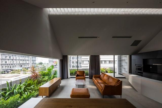 Phòng khách và bếp được kiến trúc sư thiết kế mở tạo không gian thông thoáng. Khu vực tiếp khách bày trí nội thất gỗ giản đơn, cùng ghế sofa bọc da nâu.