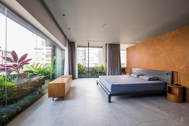 Phòng ngủ thiết kế tối giản với tường kính bao quanh. Việc tiết chế nội thất cũng giúp không gian phòng thêm rộng rãi.