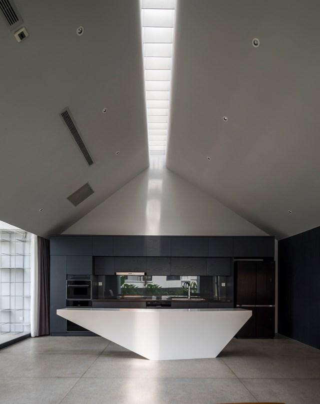 Phòng bếp được thiết kế kiểu chữ L, kết hợp với tủ bếp màu đen, đảo bếp trắng tạo tạo ra sự tương phản ấn tượng.
