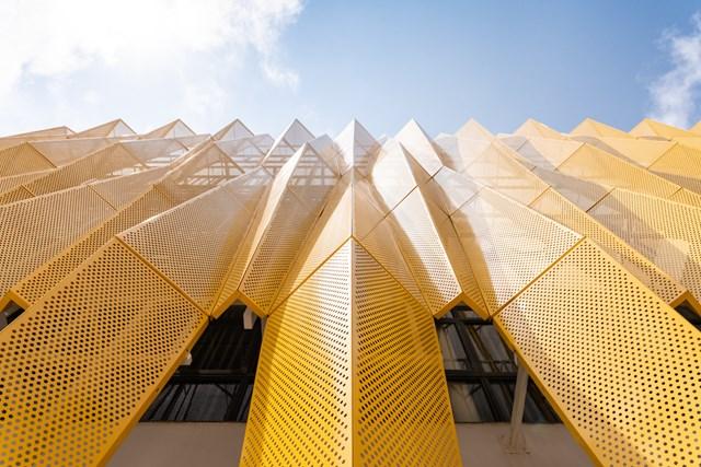 Để giải quyết ảnh hưởng nhiệt độ cao gây ra bởi ánh nắng mặt trời chiếu thẳng vào tòa nhà, giới kiến trúc sư đã thiết kế cấu trúc kép gồm các bức tường kính và tấm nhôm đục lỗ bằng đồ họa.