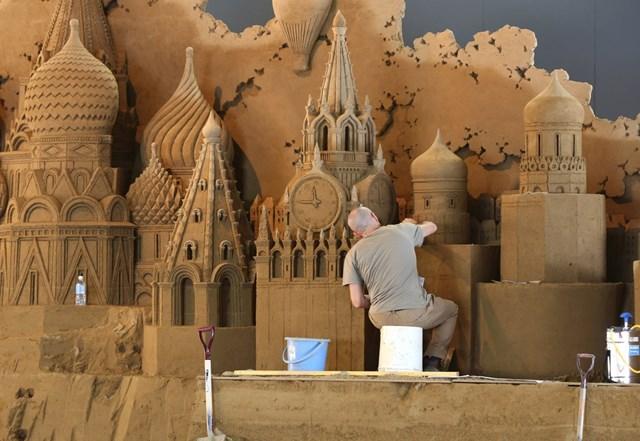 """Bảo tàng Cát Tottori (Nhật Bản) là bảo tàng trong nhà đầu tiên trên thế giới dành riêng cho nghệ thuật điêu khắc cát. Hàng năm, một nhóm nhà điêu khắc cát giỏi nhất từ khắp nơi trên thế giới cùng nhau tạo ra các tác phẩm nghệ thuật dựa trên chủ đề triển lãm năm đó. Bảo tàng đóng cửa trong 3 tháng để các nhà điêu khắc miệt mài sáng tạo. Trong hình là nhà thờ Saint Basil và điện Kremlin ở Moscow, Nga, từng bước được tạo hình bởi nghệ sĩ người Italy Leonardo Ugolini. Tác phẩm được trưng bày tại bảo tàng Cát năm 2014 trong triển lãm chủ đề """"Nước Nga""""."""