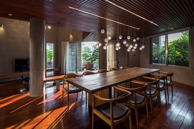 Phòng ăn chính được đặt ở tầng 2. Trần và sàn được ốp gỗ đậm màu giúp tăng cảm giác ấm cúng cho căn nhà.