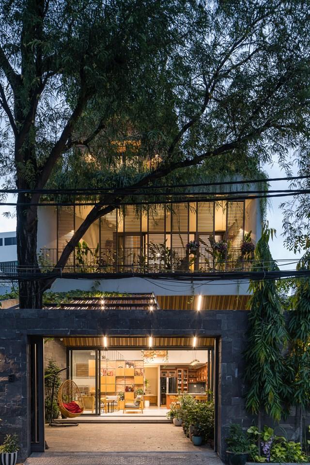 Từ ngoài nhìn vào, ngôi nhà mang lại cảm giác bình yên, ngập tràn cây xanh.(Ảnh: Quang Trần)